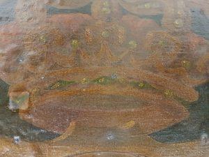 Detall d'una part del rètol on apareix representada la corona reial. Són visibles els orificis provocats pels claus.