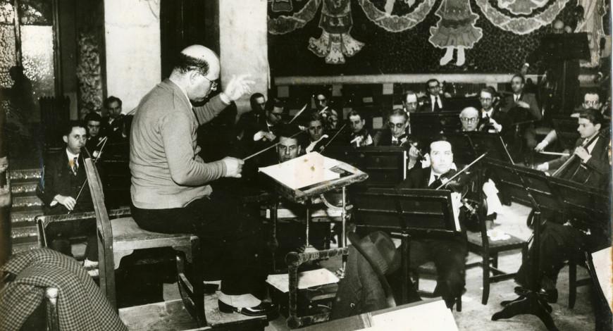 Pau Casals dirigint un assaig de l'Orquestra Pau Casals al Palau de la Música Catalana. Autor: Pérez de Rozas. 1934. Fons Pau Casals.