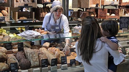 Madre e hijo comprando pan en una panadería
