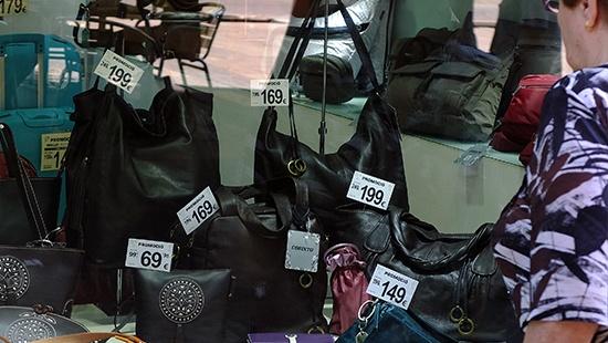girl looking at a bag shop display