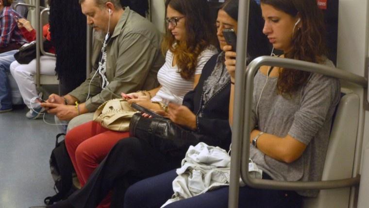 Persones mirant el mòbil al metro