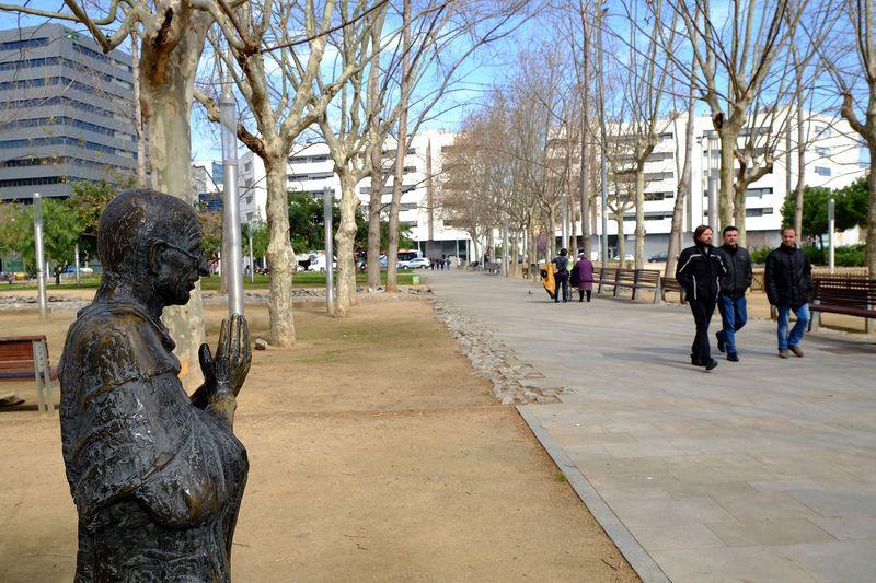 jardins de Gandhi amb l'escultura de Gandhi i un grup d'homes passejant pel costat