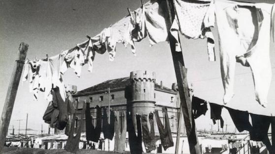 Castell del Camp de la Bota amb roba estesa de les barraques abans existentes. 1950 aprox.