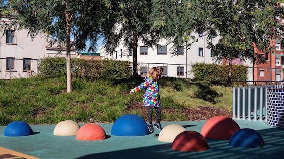 Una nena jugant al districte de Sants-Montjuïc