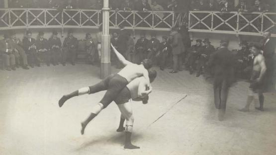 Black and white photo, public in circle and two men doing the Greco-Roman fight in the center