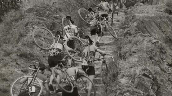 Black and white photo of cyclists carrying bikes on their backs to climb a hill during the Cross-cycle-pedestrian Catalonia Championship. Shortcut of Vallvidrera